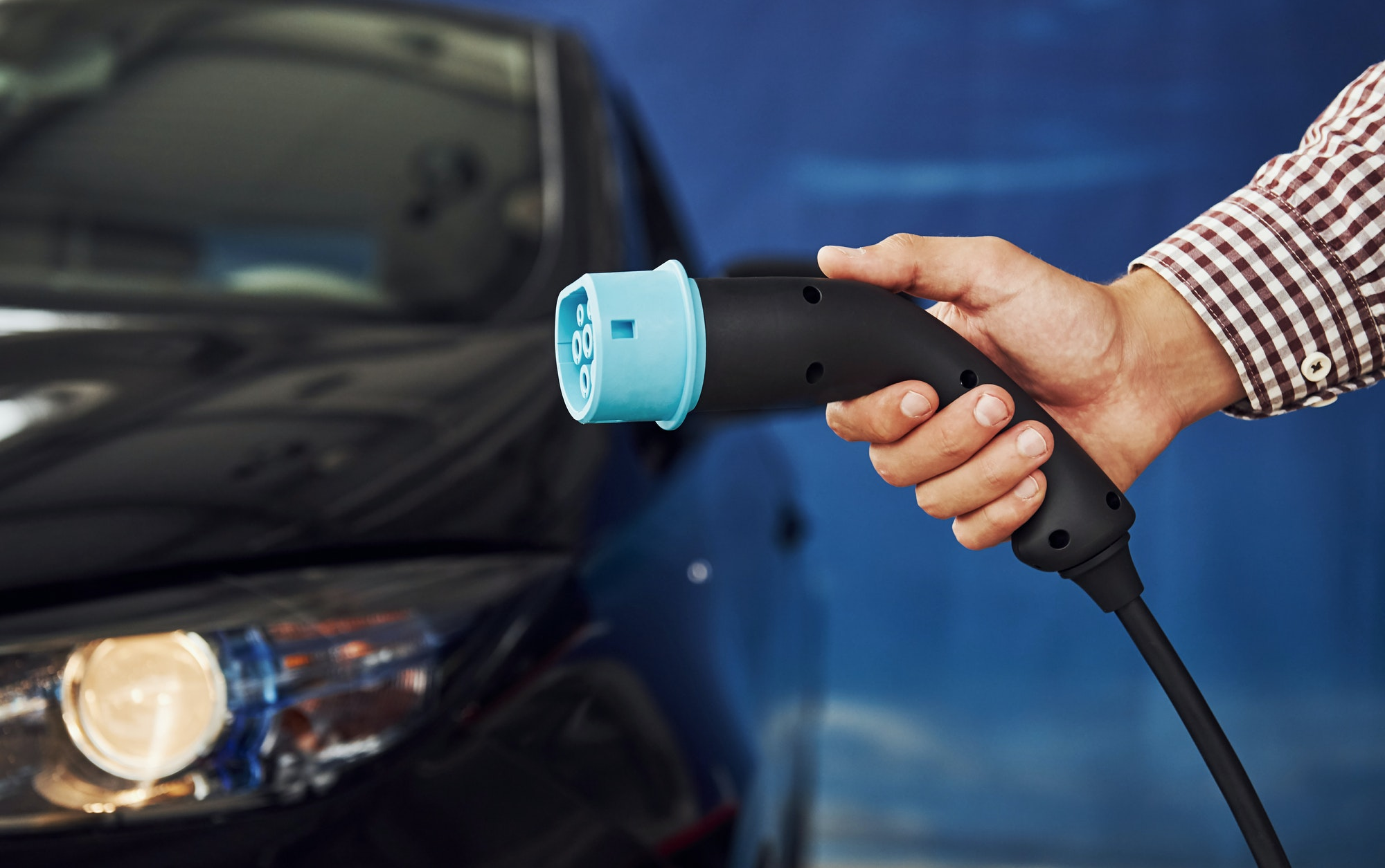 Man stands against an electric car and holds the charging cable